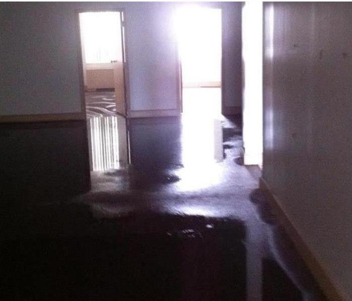 Commercial Water damage office space with standing water from pipe leak